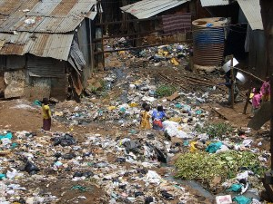 Children rummage through garbage heaps between houses in Kibera