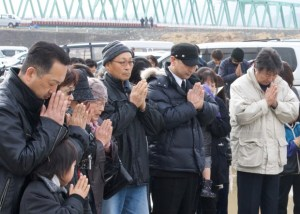 Residents pray at the school in Ishinomaki, Japan where 84 children and staff were killed in the tsunami, March 11, 2011